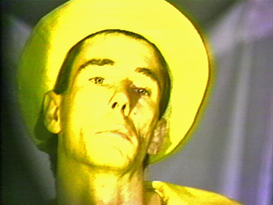 Mike Kelley, Visual Arts Center, close-up film still of yellow man in yellow hat